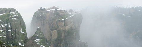 Greece. Meteora monastery in winter fog. Panorama. Greece. Meteora monastery in a winter fog. Panorama. Monastery is located on the top of steep mountain Royalty Free Stock Images