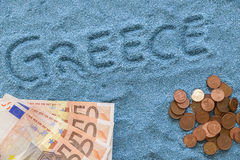 Greece money. Greece written on the sand blue with money royalty free stock photography