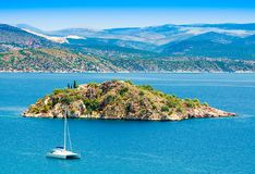 View of the sea on Tolo with a small island and a catamaran stock photos