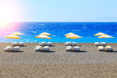 Greece, reed umbrellas and yellow sunbeds on pebble beach at Aegean Sea of Rhodes, Stock Image
