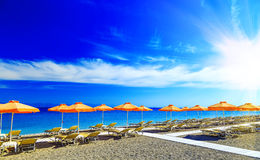 Greece, reed umbrellas and yellow sunbeds on the pebble beach at Aegean Sea of Rhodes, Greece Royalty Free Stock Photography