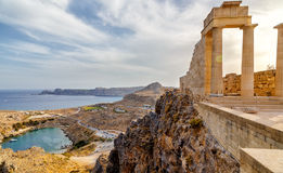 Greece. Rhodes. Acropolis of Lindos. Doric columns of ancient Temple of Athena Lindia the IV century BC and the bay of Royalty Free Stock Photo