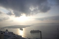 Beautiful panoramic view from touristic Fira town to caldera and volcano and cruise ship at sunset. Santorini Island, Thira, royalty free stock images