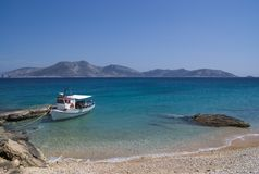 Greece, A solitary fishing boat. The island of Keros in the background. royalty free stock photography