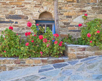 Greece,  stone wall with blue window and flowers Stock Photography