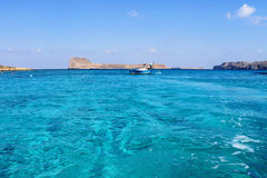 Greece. In the summer, two boats near the island in the blue lagoon Stock Image