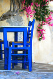 Greece, Syros island, tavern. Chairs and table and bugainvillea in the background from traditional greek taverna from Ano Syros on the island of Syros, Greece Royalty Free Stock Photo