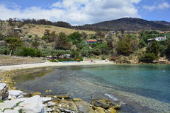 Greece, Thassos Island. Aliki, Greece - June 10, 2017: Unidentified people on tiny beach and forest damaged from forest fire 2016 on Thassos island royalty free stock photo