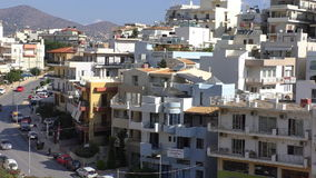 Greece town street transport. Elevated view of street transport and houses of Greek city on the hills of Agios Nikolaos with mountains in a background stock video footage