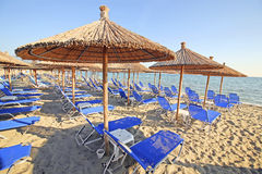 Greece, umbrellas and sunbeds. Greece, reed umbrellas and blue sunbeds on the beach Stock Image