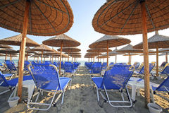 Greece, umbrellas and sunbeds. Greece, reed umbrellas and blue sunbeds on the beach Royalty Free Stock Images