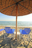 Greece, umbrellas and sunbeds. Greece, reed umbrellas and blue sunbeds on the beach Royalty Free Stock Photos