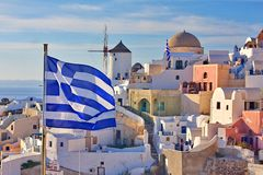 Greece welcomes you. Greece flag spotted on the view of ancient city Oia with traditional mill on background Royalty Free Stock Photos