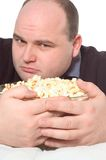 Greed. Man holds a bowl of popcorn Stock Image