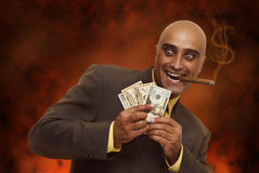 Greed. Devilish businessman in hell, counting money Stock Image