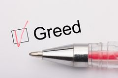 Greed - checkbox with a cross on white paper with pen. Checklist concept. Close-up royalty free stock photography