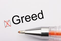 Greed - checkbox with a tick on white paper with metal pen. Checklist concept. Close-up royalty free stock image