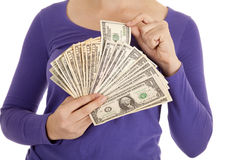 Greed close up pulling out money. A woman pulling out a 100 dollar bill out of her big money fan Stock Photography