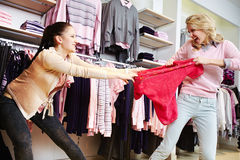 Greed. Female shoppers fighting for the last tanktop in department store Royalty Free Stock Photo