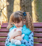 Greedy angry little girl. Sitting on a bench with a toy in the hands of Stock Images
