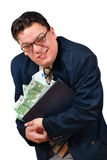Greedy business man. Greedy salesman holding on to his laptop PC stacked with euro bank notes with an apparent grimace of a lucrative but slick sale Royalty Free Stock Image