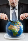 Greedy businessman cutting planet Earth Royalty Free Stock Image