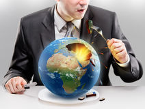 Greedy businessman eating planet Earth. Concept Royalty Free Stock Photos
