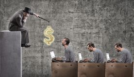 A greedy businessman motivates office workers with a salary. Office slavery concept Stock Photo