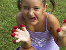 Greedy child. Plays with raspberries Stock Image