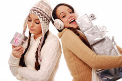 Greedy Christmas. Teenagers with christmas presents - one unhappy with just one gift and one greedy with a stack of gifts Stock Photos