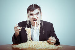 Greedy consumerism. Concept. Nasty businessman eating pasta on the table stock photography