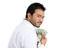 A greedy corporate businessman holding dollar notes tightly showing his possessiveness for money Stock Photography