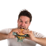 Greedy and fat businessman. Eats a sandwich with banknotes Royalty Free Stock Photo