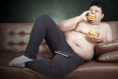 Greedy fat man eating hamburger. While watching tv at home Royalty Free Stock Photo