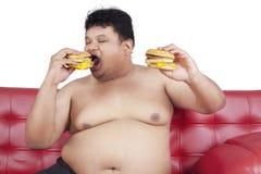 Greedy fat man eating hamburger 2 Royalty Free Stock Images