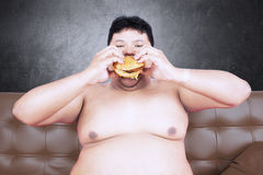 Greedy fat man with hamburger on the couch. Image of greedy fat man sitting on the brown sofa while eating delicious hamburger Stock Photo