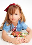 Greedy  girl with pile of sweets. Laying on the table and with troubled expression on the face Royalty Free Stock Images