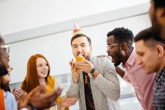 Greedy guy is trying to bite a bigger peace of cake in front of friends. Greedy guy is trying to bite a bigger peace of cake in front of hungry shocked friends Stock Photo