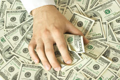 Greedy hand grabs money. Greedy hand grabs lot of dollars Royalty Free Stock Photography