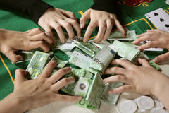 Greedy hands grabbing cash. Closeup of six greedy gamblers winning hands grabbing 100 euro banknotes cash money on a poker table Stock Photo