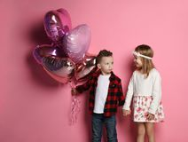 Greedy little boy doesn`t want to give the girl heart ballons, but they still hold hands stock photography