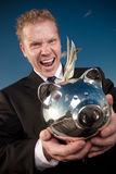 Greedy man. Holds a piggy bank with cash Stock Photography