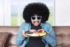 Greedy man holds a plate of donuts. Portrait of a greedy man with curly hair, sitting on the sofa while holding a plate of tasty donuts and wearing sunglasses Stock Images