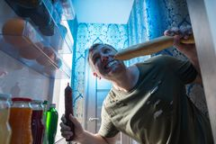 Greedy man munching a baguette and salami. Greedy man munching a baguette and whole salami in the open door of the fridge in his kitchen at night standing with a royalty free stock photo