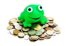 Greedy for Money (isolated). Heaps of various coins and crazy frog (concept - greedy for money) on a white background Royalty Free Stock Photos