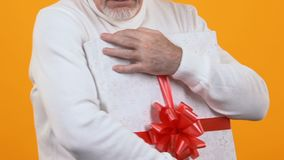 Greedy old man holding wrapped present box, capricious pensioner, souvenir. Stock footage stock footage