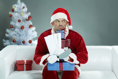 Greedy Santa. Griping Christmas presents and letters and snapping Royalty Free Stock Images