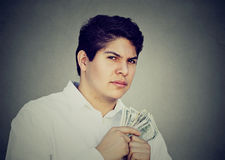 Greedy suspicious man holding money dollar bills in hand. Greedy young suspicious man holding money dollar bills in hand Royalty Free Stock Photos