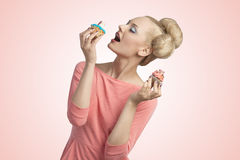 Greedy woman with cupcakes Stock Photography
