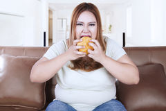 Greedy woman eats hamburger. Portrait of greedy woman eating hamburger while sitting on sofa, shot indoors Stock Photos